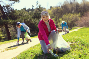 Great weekend. Alert old woman gathering litter while other volunteers helping her
