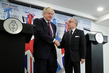 Britain's Foreign Secretary Johnson and Argentina's Foreign Minister Faurie shake hands during a news conference in Buenos Aires