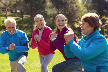 Spending time together. Delighted athletic woman smiling and training aged people in the open air