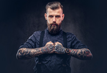 Severe old-fashioned hipster guy in a blue shirt and suspenders, posing in a studio.