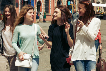 many young happy women walking talking  on background of old european city street, stylish hipster girls having fun, moments of happiness, friendship concept