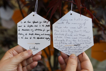 The messages left by Britain's Priince William and Prime Minister Theresa May after attending a memorial service on the first anniversary of the Manchester Arena bombing are seen in Manchester
