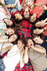happy group of women faces in circle laughing and having fun on picnic top view, lying on blanket, joyful moments celebration in summer park