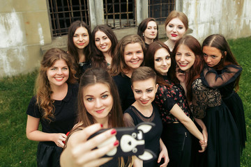 gorgeous women group in black dresses taking selfie having fun and laughing in the city. stylish lady party with gothic theme. elegant girls