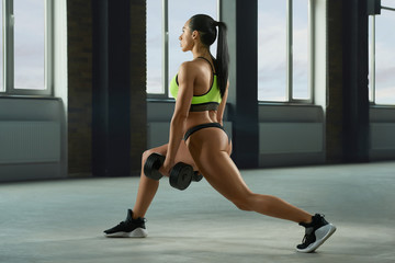 Athletic girl performing fallouts keeping dumbbells in spacy gym with panoramic windows. Having strong, fit body with heatlthy tanned skin, muscles. Doing fitness exercises. Wearing modern sportswear.