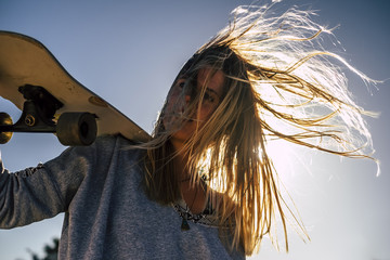 long blonde hair moved by the wind in a summer day of vacation for beautiful blonde model with skateboard . rebel and freedom independent traveler concept Fototapete