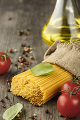 Italian food background with vine tomatoes, basil, spaghetti, olive oil. Top view