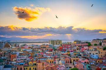 Sunset on Cagliari, panorama of the old city center with traditional colored houses with beautiful yellow-pink clouds and seagull's in the sky, Sardinia Island, Italy