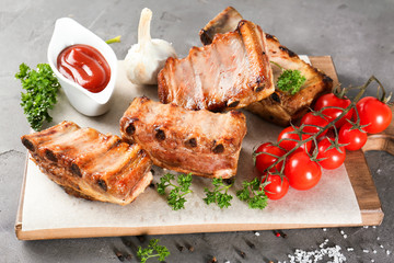 Wall Mural - Wooden board with delicious grilled ribs, tomatoes and sauce on table