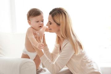Woman applying body cream on her baby indoors