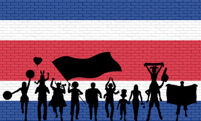 Costa Rican supporter silhouette in front of brick wall with Costa Rica flag