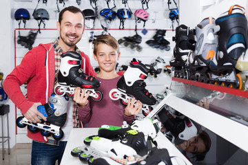 Smiling father and son boasting roller-skates