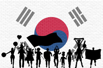 Korean supporter silhouette in front of brick wall with South Korea flag