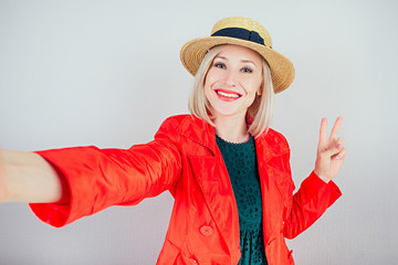 beautiful girl traveler in a red coat and hat doing selfie on the phone on a white background