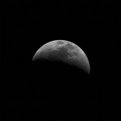 Little growing Moon rise from dark background in space, taken with newtonian telescope.