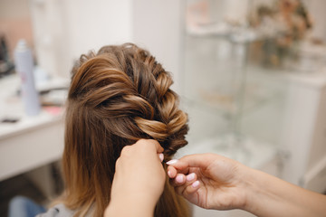 Close-up of woman hairdresser weaving plaits in beauty salon.