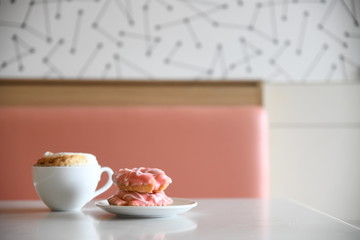 Close-up coffee and donuts on cafe table