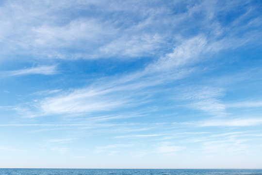 Beautiful blue sky over the sea with translucent, white, Cirrus clouds