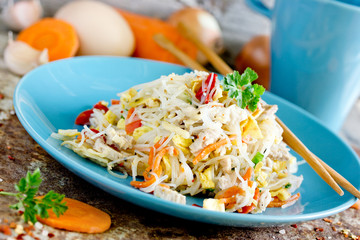 Pan fried rice noodles with fried eggs, chicken and vegetables