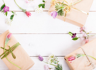 Gift and pink flowers on wooden white background. Workspace. Backdrop with copy space, flat lay, top view. Mother's, Valentines, Women's, Wedding Day concept.