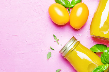 Useful and healthy smoothie or juice from yellow tomatoes and bell peppers with green basil and oregano in glass bottles, pink background, top view