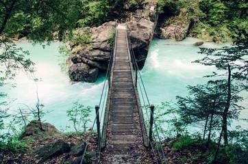 Suspension bridge over beautiful blue apline river Soca, popular outdoor destination, Soca Valley, Slovenia, Europe