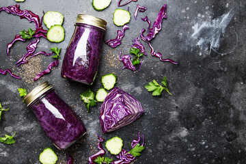 Healthy and useful detox smoothies or juice from red cabbage, cucumbers with chia seeds in glass bottles on a gray background, top view