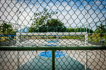 basketball court and soccer field in public park behind fence -