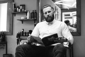 Portrait of handsome bearded man with fashionable hairstyle and beard at barber shop. He chooses a haircut in the journal.