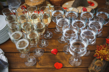 Wedding glasses filled with champagne, water stand on wooden table.