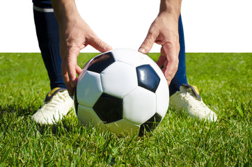Close up legs of football player in blue socks and white shoes holding the ball in his hands placing it at the free kick or penalty spot playing on grass pitch isolated on white background