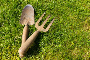 Old and weathered garden trowel and fork on a green grass background - copy space provided
