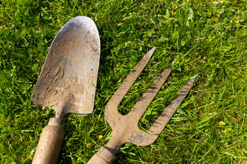 Old and weathered garden trowel and fork on a green grass background