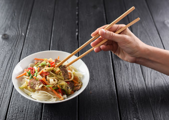 Slender woman hand with chopsticks reaching for Asian udon noodles with meat and vegetables on black background copyspace. Minimalist style