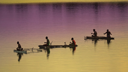 Unrecognizable local fishermen fishing in small wooden boats at colorful sunrise