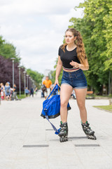 Young woman riding roller skates holding bag