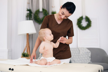 A little funny baby having massage with professional female masseuse. Сhildren's massage on the couch in a modern cozy room. Kind and friendly children's doctor.