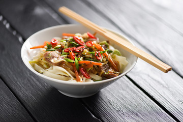 Traditional Asian noodles in minimalist style. Healthy nutritious meal of udon noodles, meat, vegetables, chili and spring onion in white bowl with chopsticks on black background copyspace