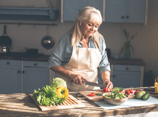 Portrait of calm senior woman is making salad while listening to music from earphones. She is standing at table in kitchen and smiling