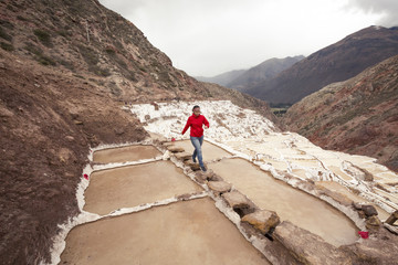 Woman walking on salt pans, Maras, Cusco region, Peru