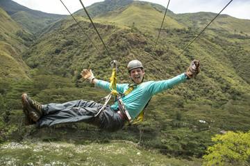 Man riding on zipline through Amazon forest, Santa Teresa, Cusco region, Peru