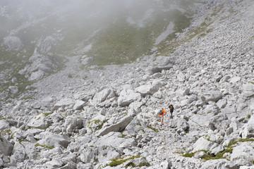 Two hikers are walking in rocky terrain of Mount Krn in Julian Alps of Slovenia