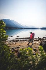 Woman backpacking along shore of Lake Garibaldi, British Columbia, Canada