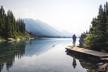 Woman backpacking along shore of Lake Garibaldi, British Columbia, Canada