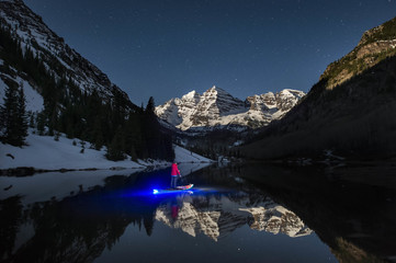 Paddleboarder crossing mountain lake at night, Aspen, Colorado, USA