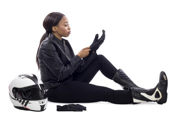 Black female racer or biker or stuntwoman sitting with a racing helmet and gear.  The gritty woman driver is isolated on a white background.