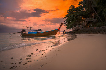 exotic tropical koh phi phi island - beach in front of beautiful purple orange sunrise sunset with clouds on sky