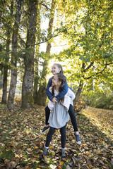Girl giving sister piggyback ride in park