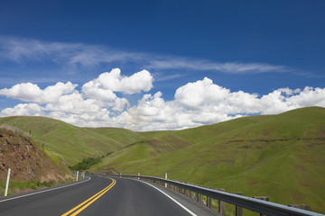 Scenery of country road and green rolling hills under blue sky with clouds, Palouse, Washington State, USA