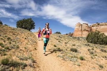 Women trail running through Grand Staircase-Escalante National Monument, Utah, USA